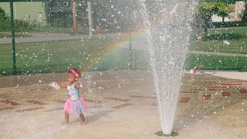 Little angels, in the glow of a rainbow, cools off at Fannie Lewis Plaza spray basin in Cleveland