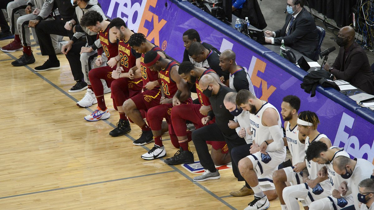 The Cleveland Cavaliers and the Memphis Grizzlies kneel with their arms linked before an NBA...