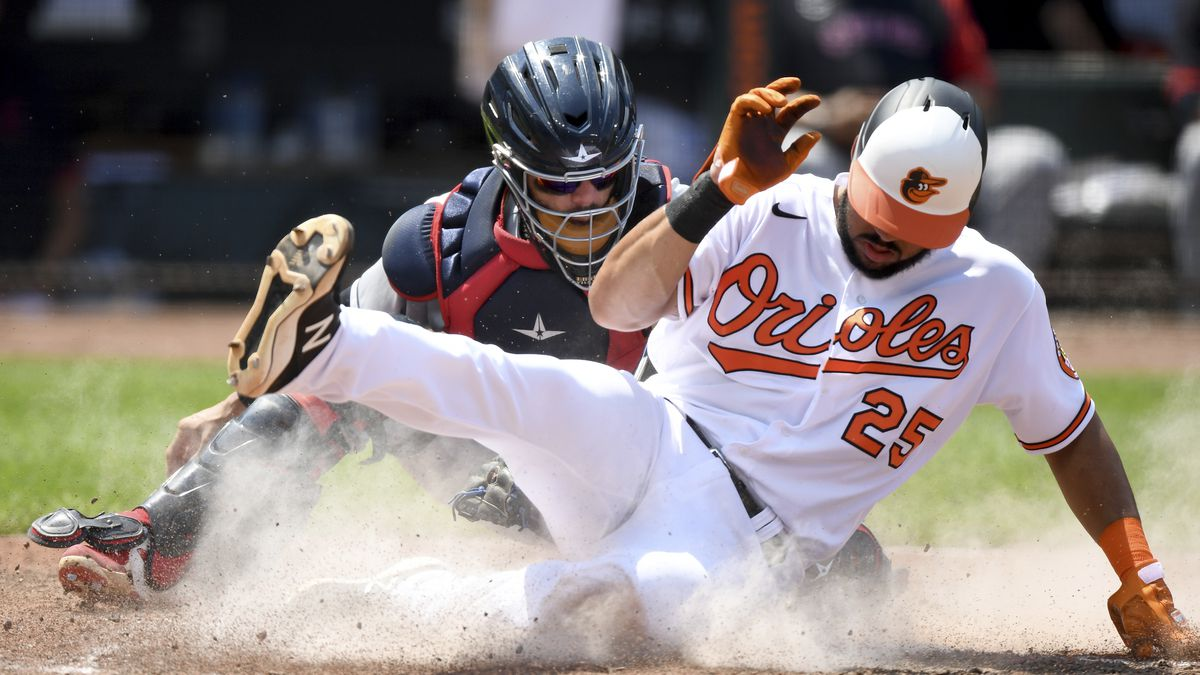Baltimore Orioles' Anthony Santander, right, slides safely across home plate to score in front...