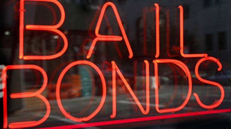 In this photo taken Tuesday, July 7, 2015, a sign advertising a bail bonds business is...