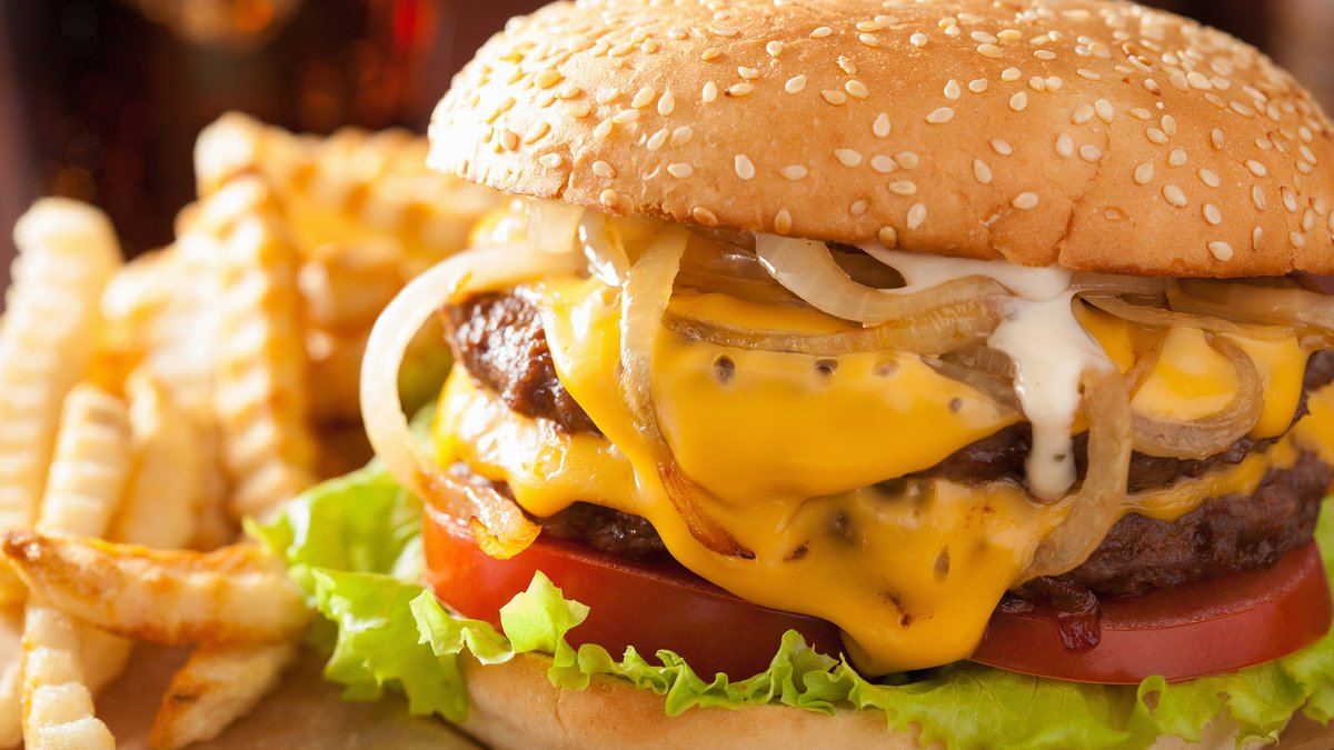 A double cheeseburger with tomato and onion is one way to enjoy International Hamburger Day.