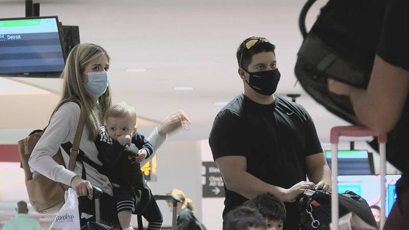 Travelers at Cleveland Hopkins International Airport wear masks at baggage claim