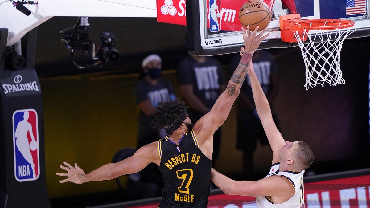 Los Angeles Lakers' JaVale McGee (7) drives to the basket over Denver Nuggets' Nikola Jokic,...