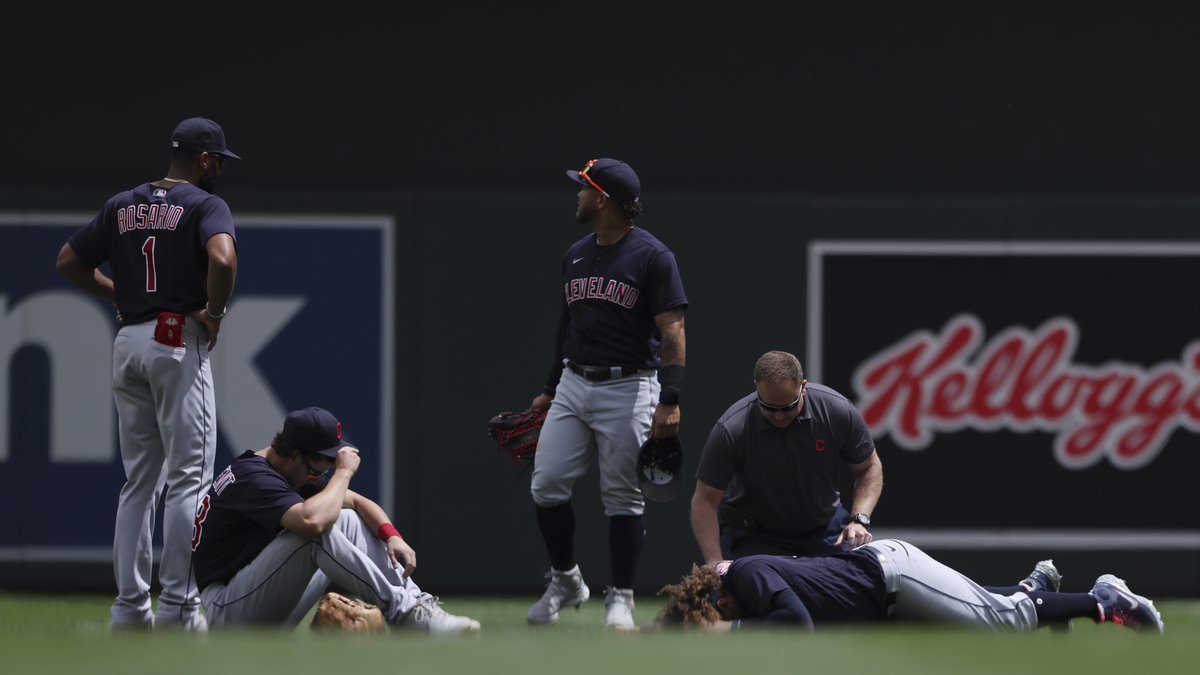 Cleveland Indians' Josh Naylor (22) lies on the ground with a member from the Indians medical...