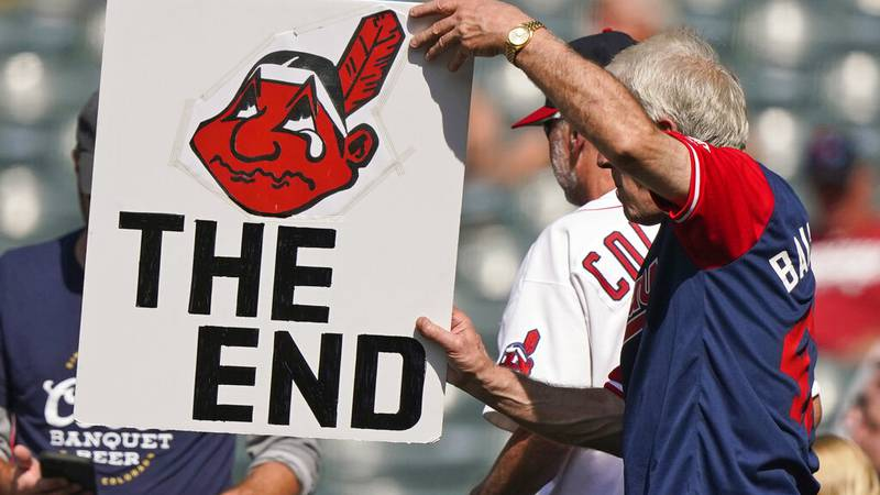 A Cleveland Indians fan holds up a sign during a baseball game between the Kansas City Royals...