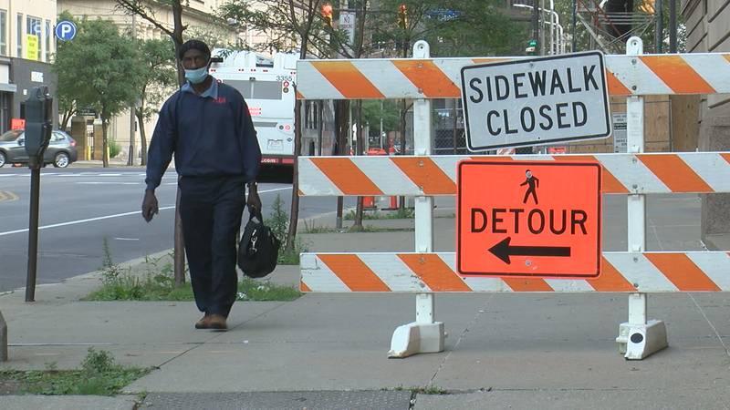 A pedestrian walks along a sidewalk detour in downtown Cleveland