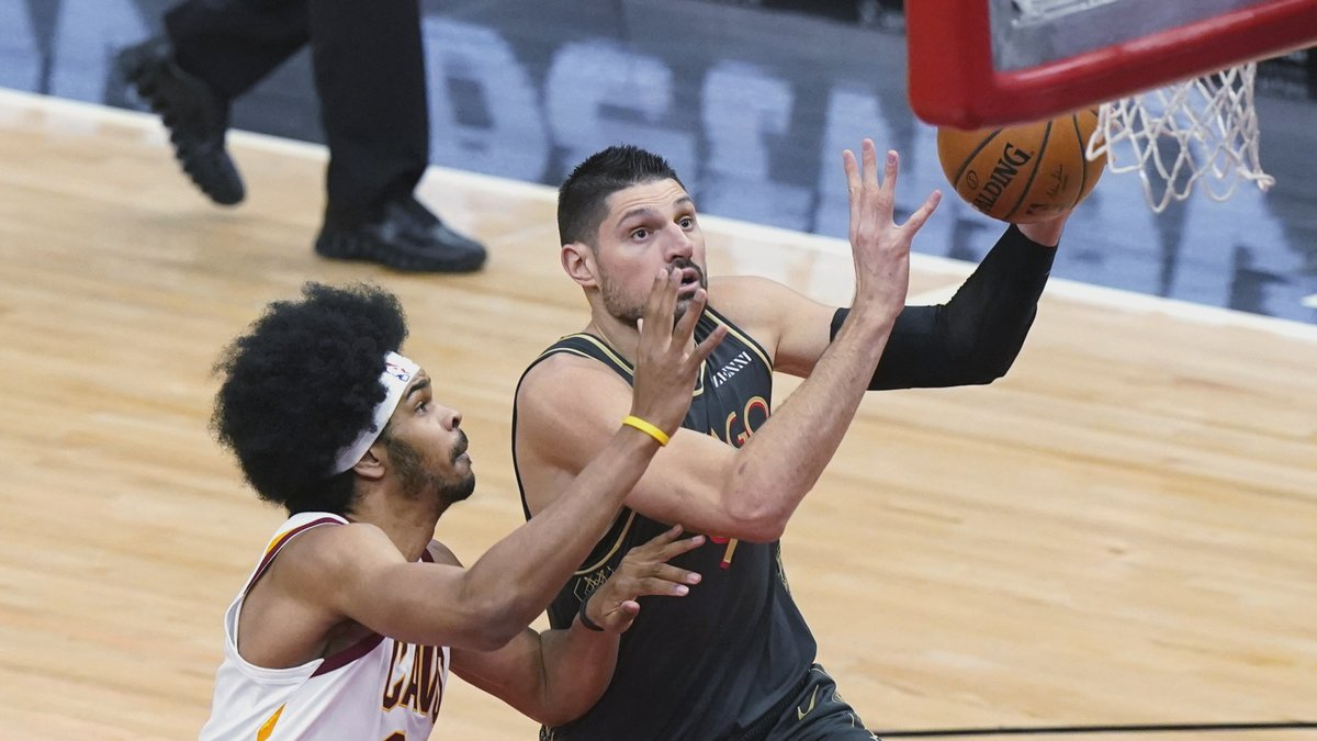 Chicago Bulls center Nikola Vucevic, right, drives to the basket against Cleveland Cavaliers...