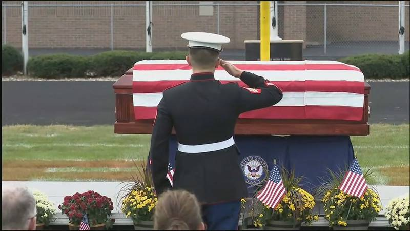 U.S. Marine Corps Sgt. Sam Roth salutes the casket of Navy Corpsman Maxton Soviak at his...