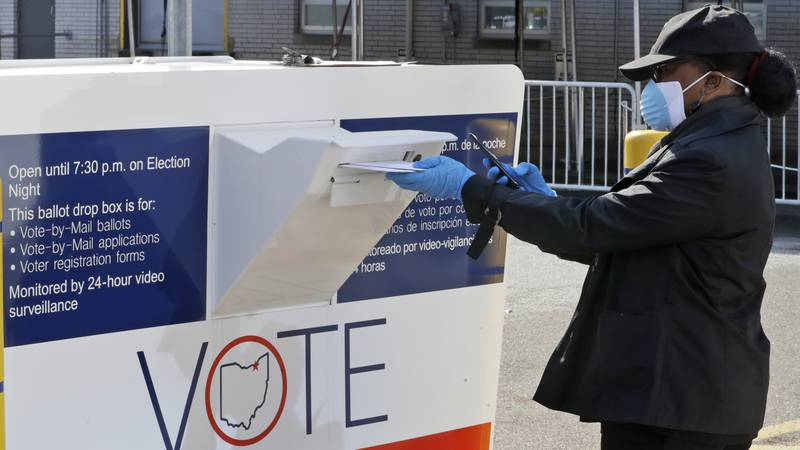 Marcia McCoy drops her ballot into a box outside the Cuyahoga County Board of Elections,...