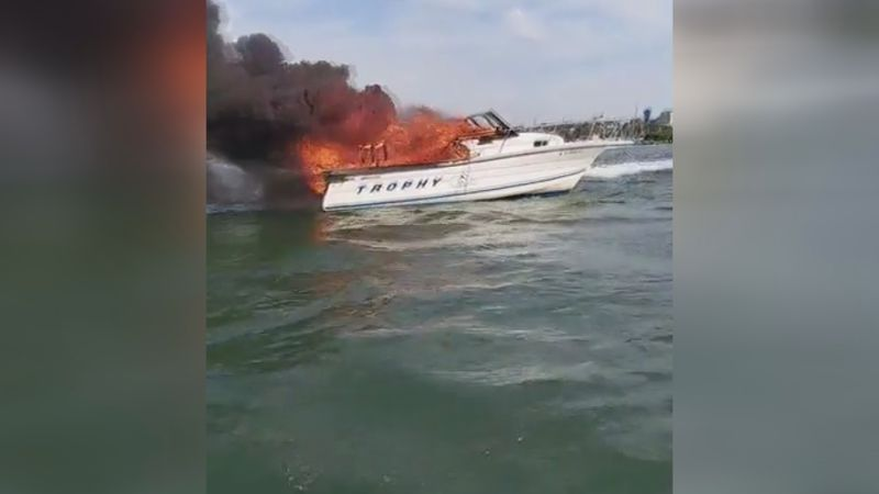 Boaters are rescued just before their boat erupts in flames.