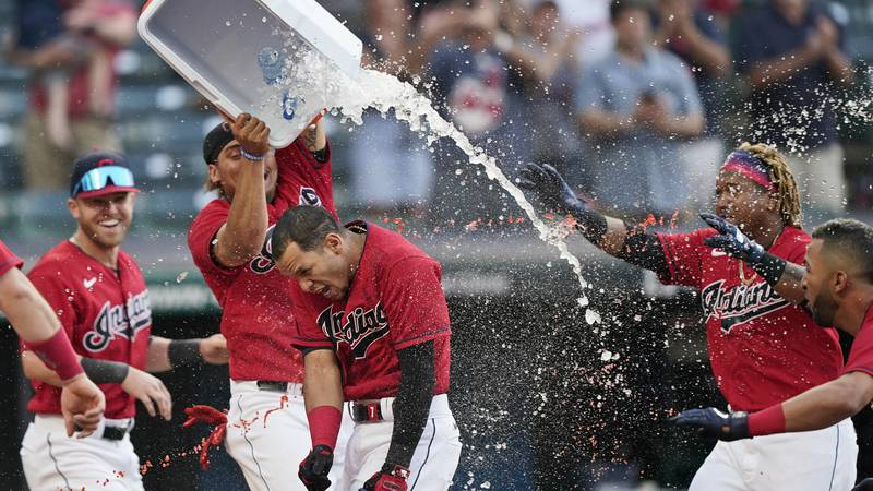 Cleveland Indians teammates douse Cesar Hernandez, center, after he hit the winning two-run...