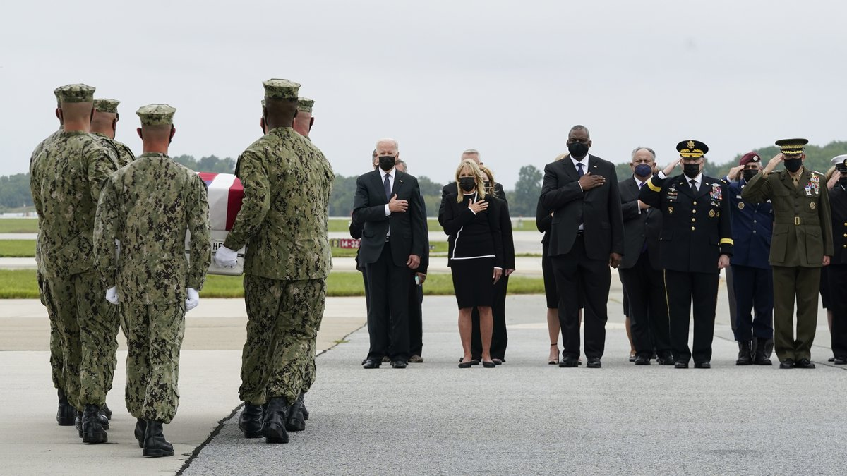 President Joe Biden watches as a Navy carry team moves a transfer case containing the remains...