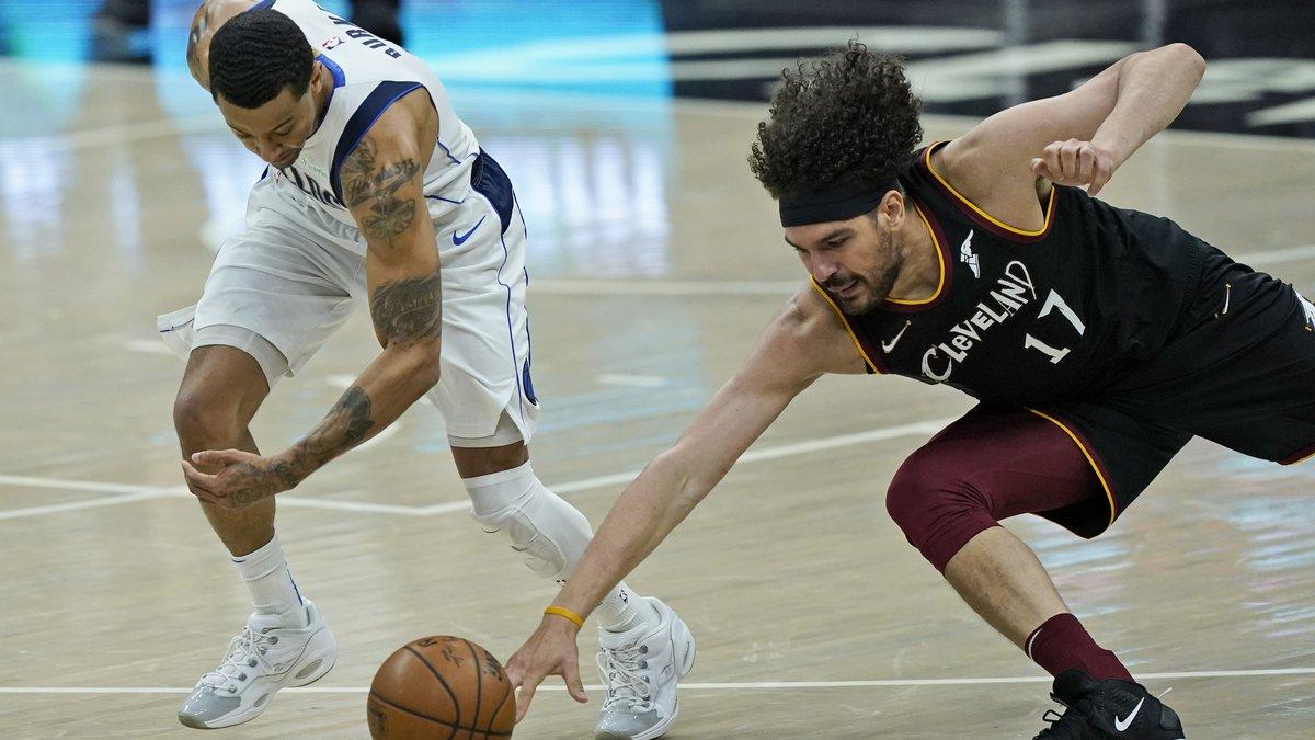 Dallas Mavericks' Trey Burke (3) and Cleveland Cavaliers' Anderson Varejao (17) battle for a...
