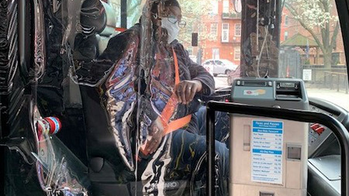 An RTA bus driver sits behind a new protective vinyl barrier to prevent the spread of illness