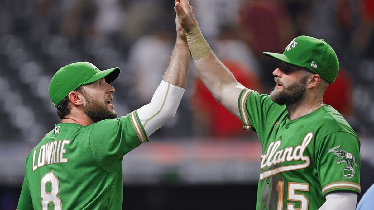 Oakland Athletics' Jed Lowrie (8) and Seth Brown (15) celebrate after the A's defeated the...