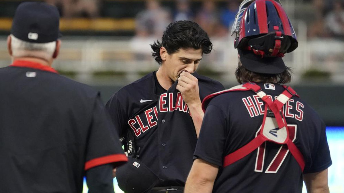 Cleveland Indians pitcher Cal Quantrill, center, gets a mound visit in the third inning of a...