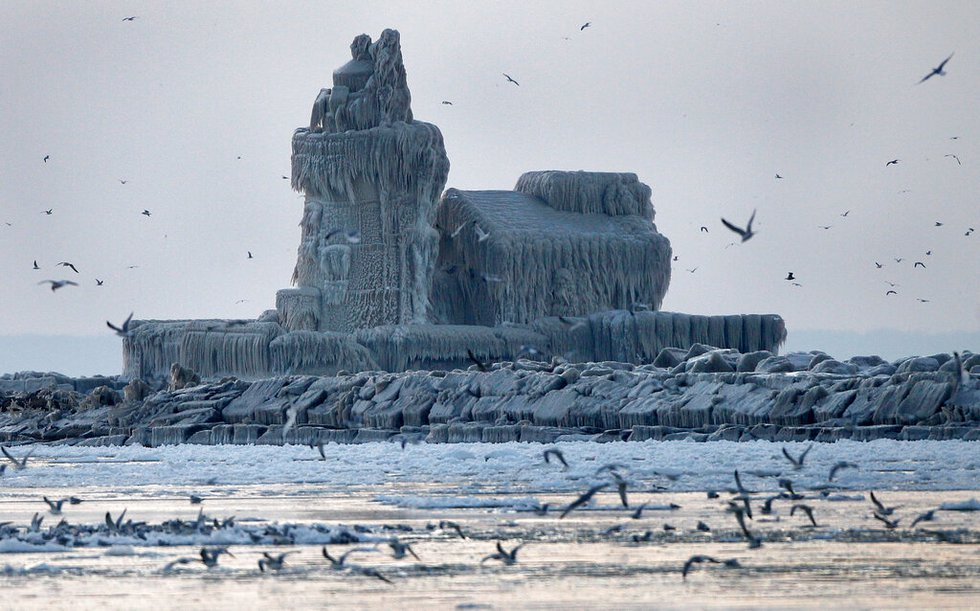 As the sun begins to set, seagulls flock to the warmer waters of Lake Erie around the...