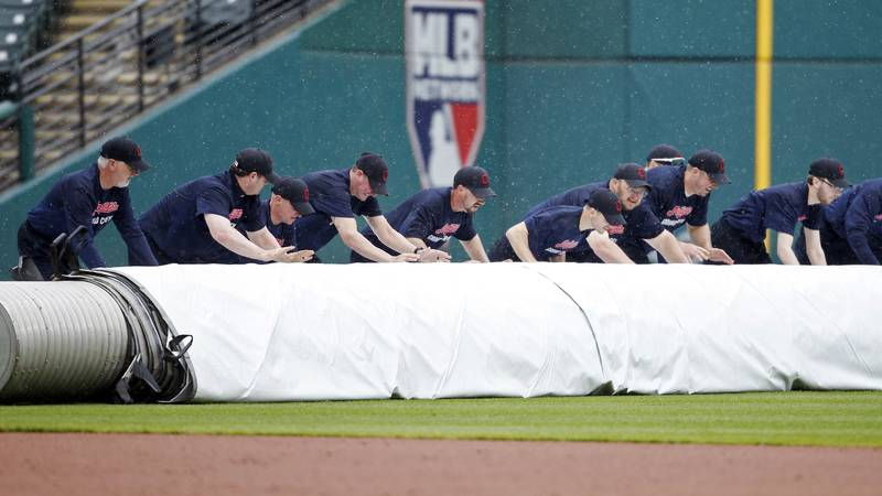 The Cleveland Indians grounds crew rolls out the tarp as rain falls after the fifth inning,...