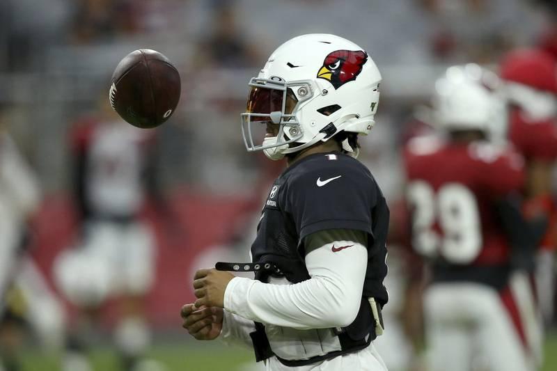 Arizona Cardinals quarterback Kyler Murray flips the ball in the air during an NFL football...