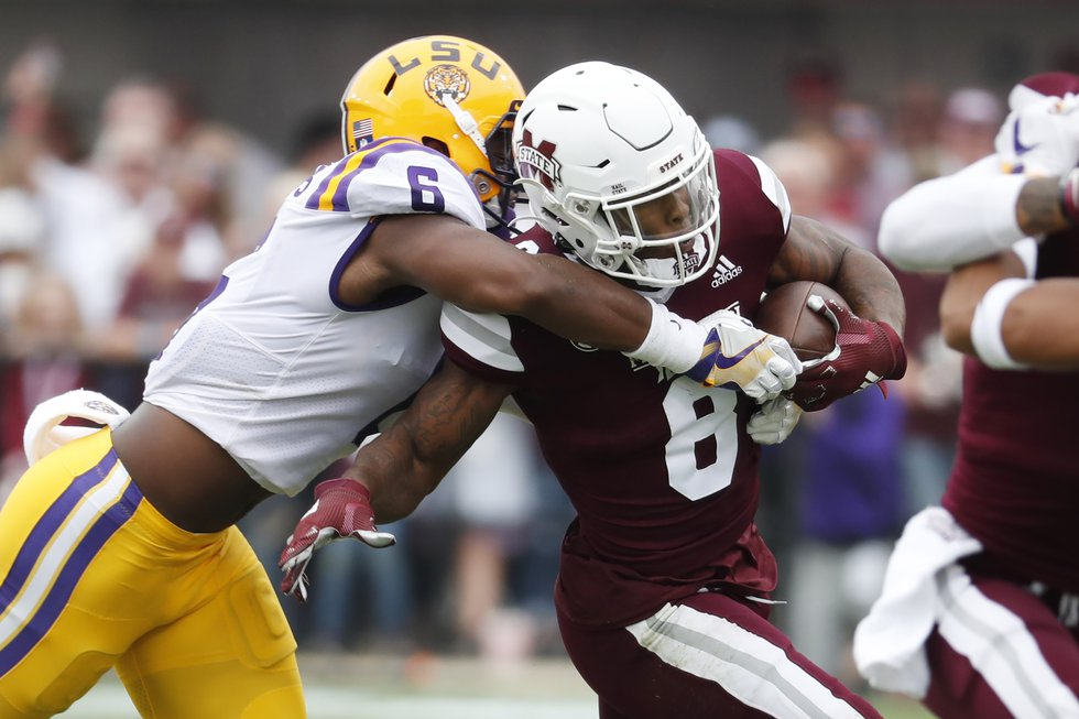 Mississippi State running back Kylin Hill (8) is tackled by LSU linebacker Jacob Phillips (6)...