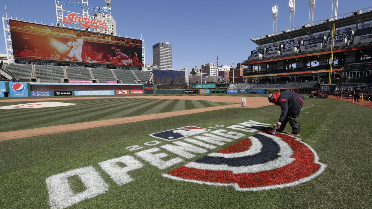 Mathew Gudin paints the opening day signage on the field before the Cleveland Indians play the...