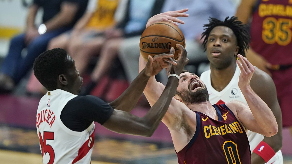 Toronto Raptors' Chris Boucher, left, knocks the ball loose from Cleveland Cavaliers' Kevin...