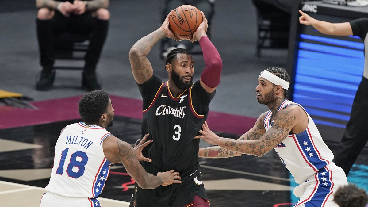 Cleveland Cavaliers' Andre Drummond (3) drives between Philadelphia 76ers' Shake Milton (18)...