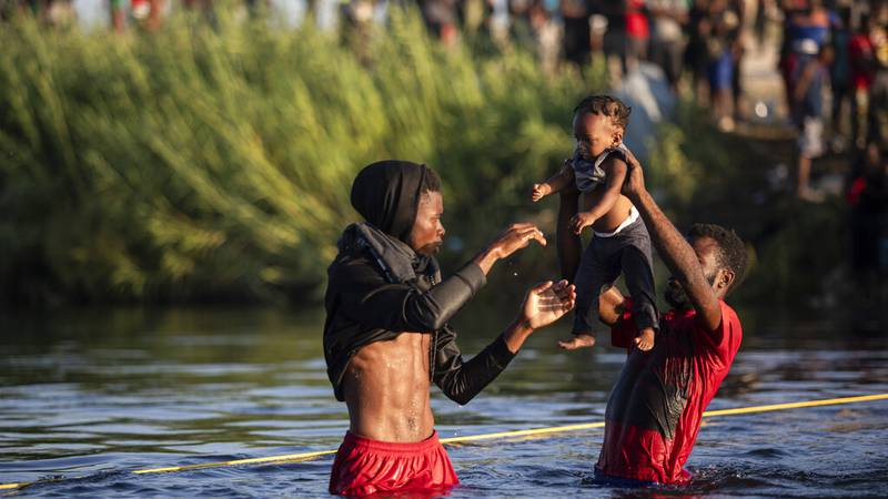 Men lift a baby over the waters of the Rio Grande river as migrants, many from Haiti, wade...