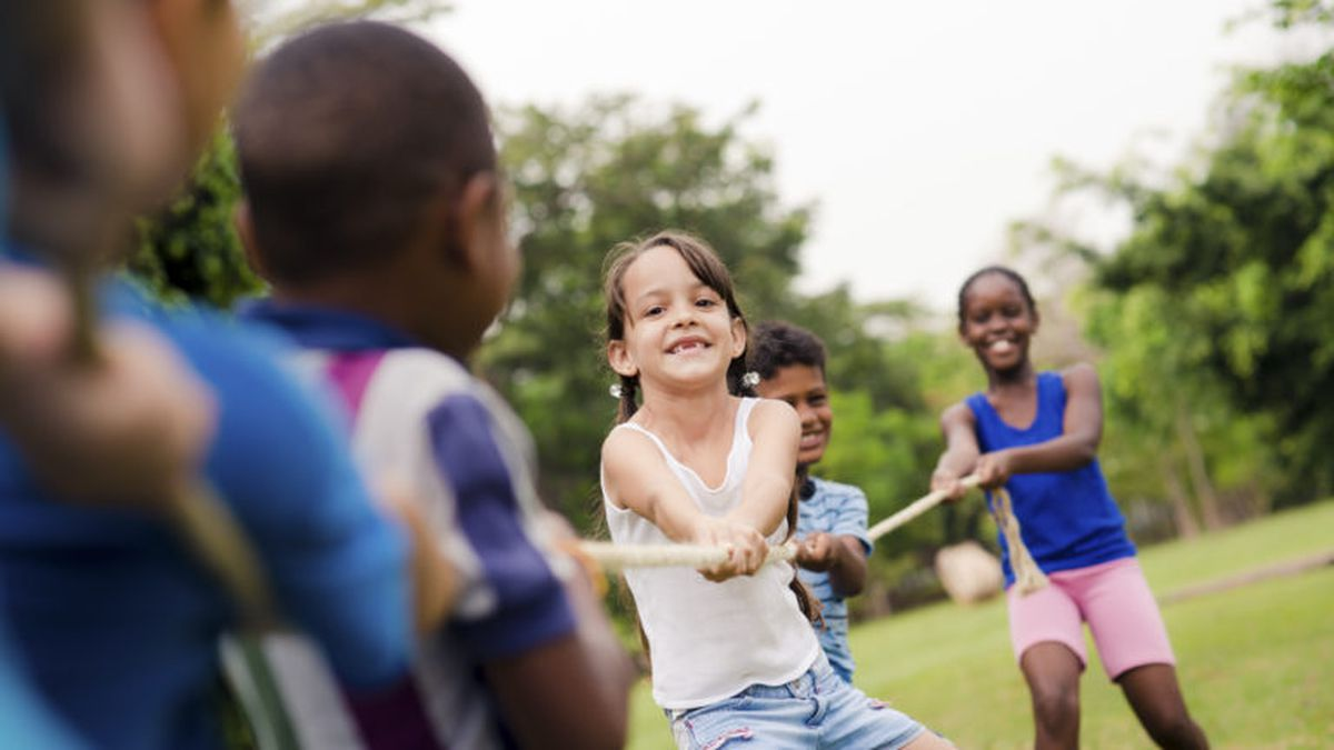 Children and recreation, group of happy multiethnic school kids playing tug-of-war with rope in...