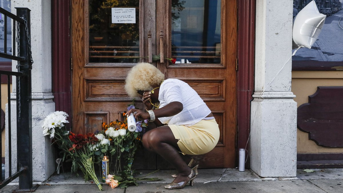 Mourners place flowers and candles at the front of Ned Peppers bar while they gather at the...