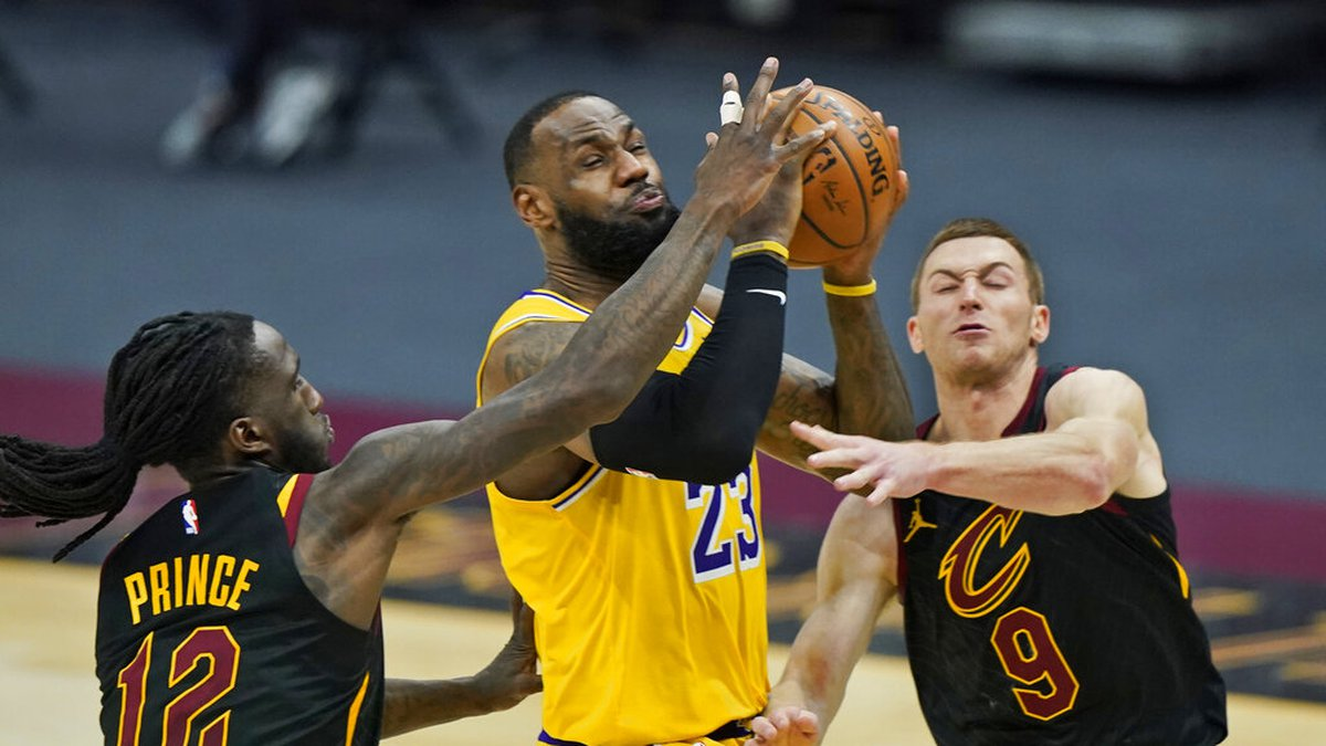 Los Angeles Lakers' LeBron James (23) drives to the basket between Cleveland Cavaliers' Taurean...
