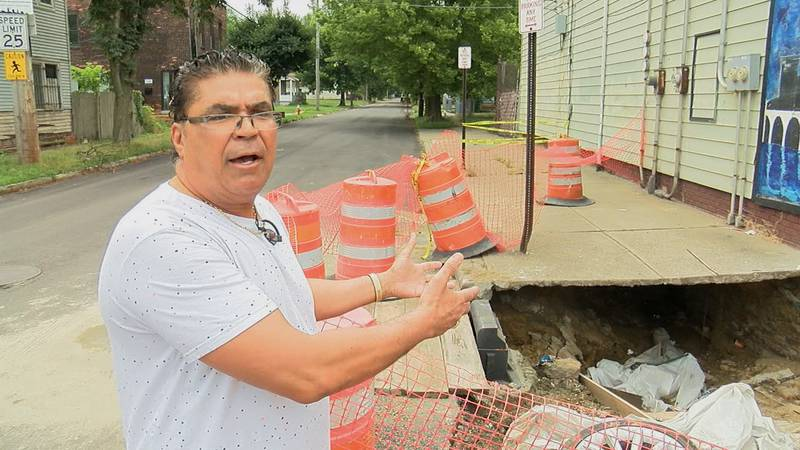 Sam Awad gestures toward a gaping hole beside his corner market in Cleveland.