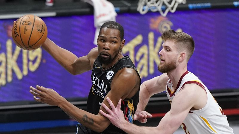 Brooklyn Nets' Kevin Durant, left, drives past Cleveland Cavaliers' Dean Wade during the first...
