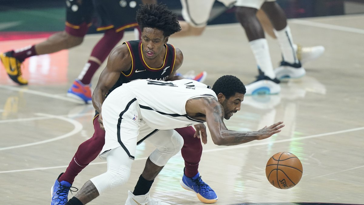 Brooklyn Nets' Kyrie Irving, right, drives past Cleveland Cavaliers' Collin Sexton during the...