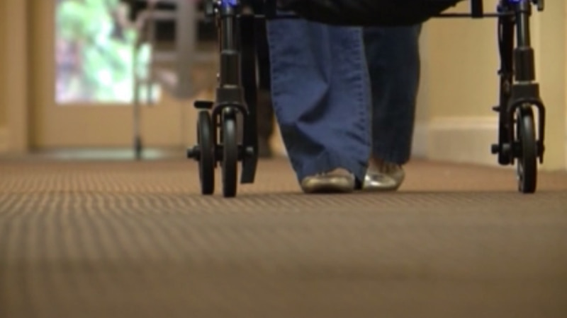 Unidentified nursing home resident uses a walker.