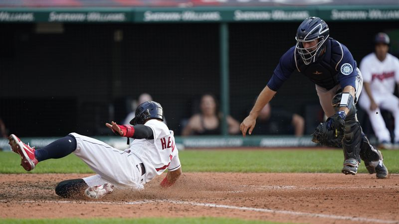 Cleveland Indians' Cesar Hernandez, left, scores as Seattle Mariners catcher Tom Murphy is late...