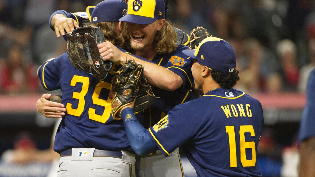 Milwaukee Brewers starter Corbin Burnes (39) hugs reliever Josh Hader as they celebrate after...