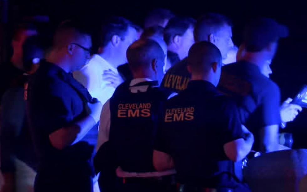 Cleveland EMS and police crowd around the water's edge Wednesday night in the hopes of spotting...