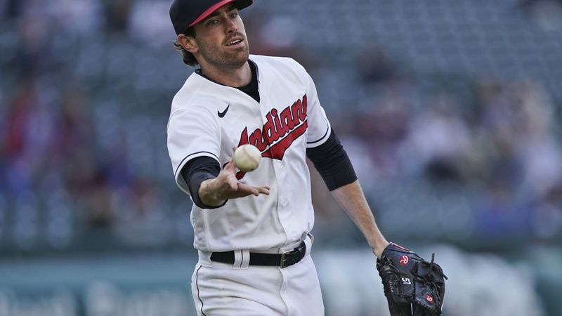 Cleveland Indians starting pitcher Shane Bieber tosses the ball to first base to get Chicago...
