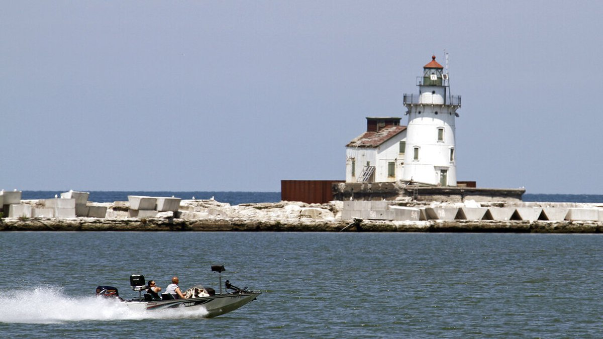 Two fishermen in a bass boat speed past the harbor lighthouse in Cleveland Wednesday, May 23,...