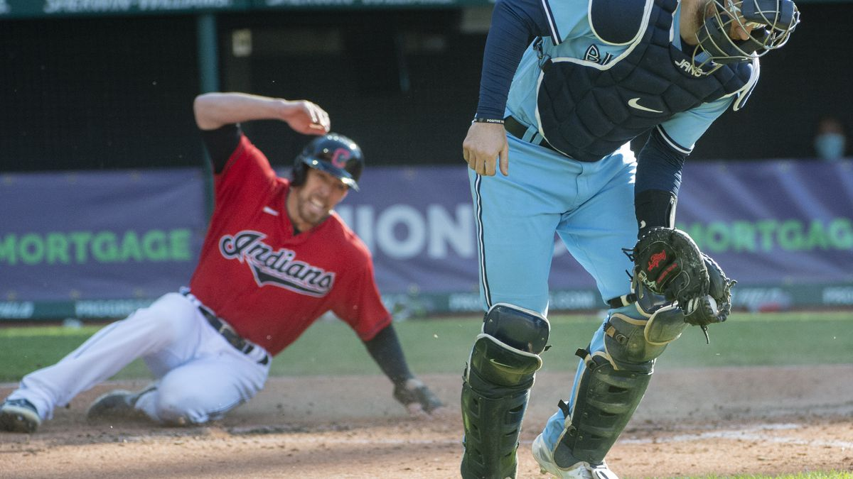 Toronto Blue Jays' Danny Jansen catches the throw but too far from home plate to tag Cleveland...