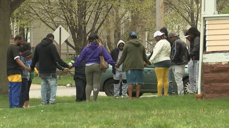 Family and friends of Trayvon Johnson bow their heads in prayer after he was shot by a federal...