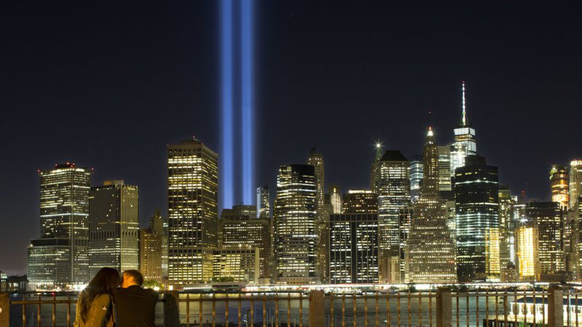 A couple embraces on the Brooklyn Promenade as the Tribute in Light rises above the lower...