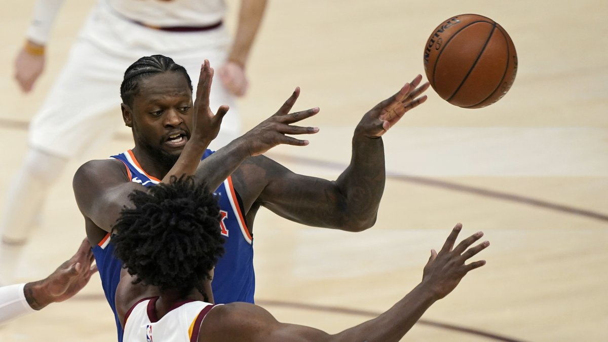 New York Knicks' Julius Randle, back, passes the ball away from Cleveland Cavaliers' Collin...