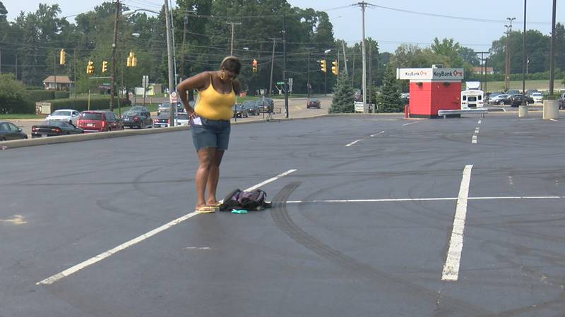 A woman stands near the spot where her nephew was killed in Akron