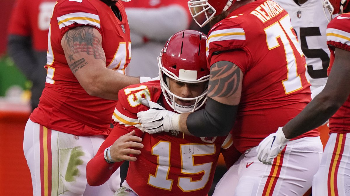 Kansas City Chiefs quarterback Patrick Mahomes (15) is helped off the field by teammate Mike...