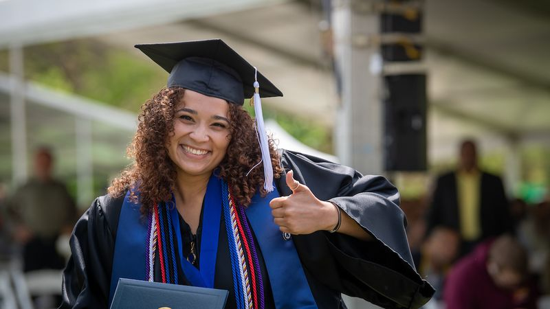A new Kent State University graduate gives a thumbs-up after receiving her degree at her spring...