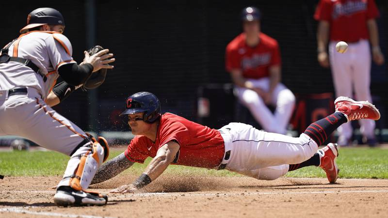 Cleveland Indians' Yu Chang, right, slides safely into home plate as Baltimore Orioles' Austin...