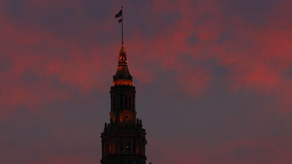 The sky turns pink as the sun sets beyond the Terminal Tower in downtown Cleveland (AP...