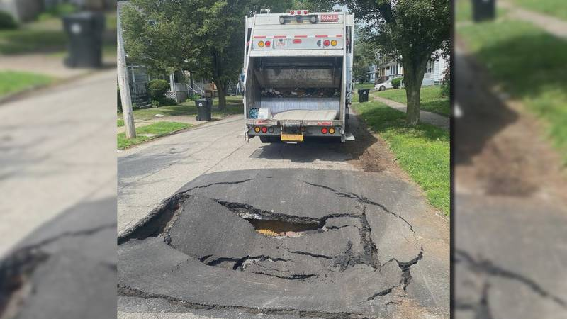 A city garbage truck stops after a massive sinkhole opened on Everton Road on Cleveland's East...